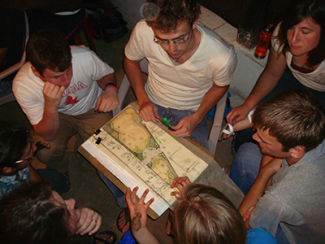 students at night gathered around a design plan
